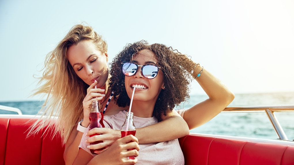 Two friends sip on soda while riding on a boat with red seats, and laughing on vacation.