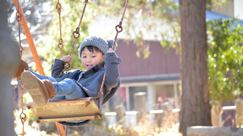 Kid on a swing in a winter park