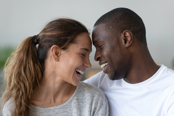 Head shot multiracial young married spouse laughing, cuddling hugging embracing bonding together, touching foreheads, demonstrating support, love, tender moment. Dating romantic relations concept.