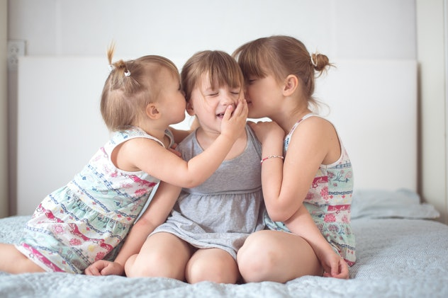 Three sibling sisters on a light background in a real interior. Concept relationships and lifestyle