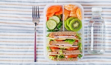 School lunch box with sandwich, vegetables, water, and fruits on table. Healthy eating habits concep...