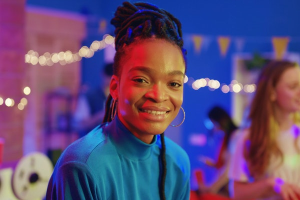 Lovely cheerful afro-american beautiful girl smiling happy at camera enjoying celebration socializing event party with best friends.