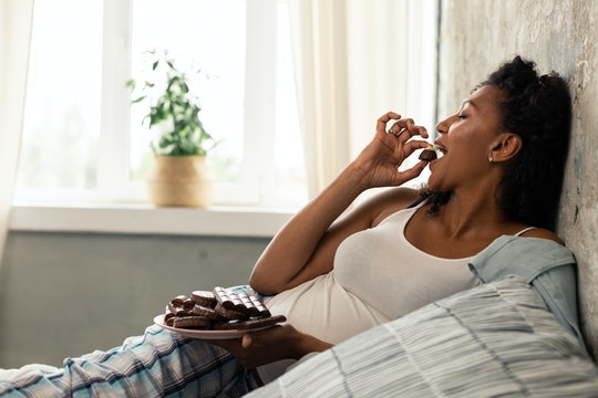 woman laying in her bed eating chocolate candies.