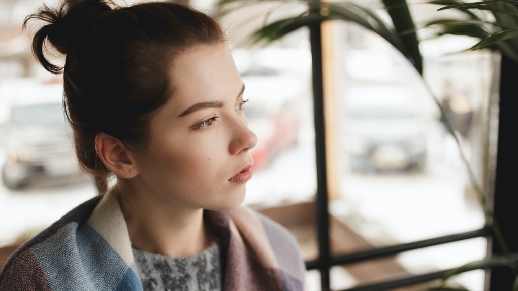 Woman in pullover sadly looking at window in a cafe