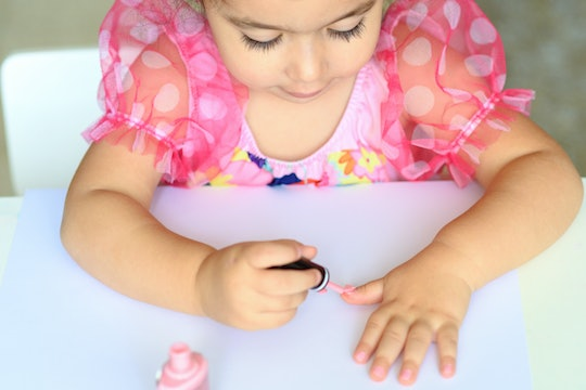 a little girl painting her nails with pink nail polish
