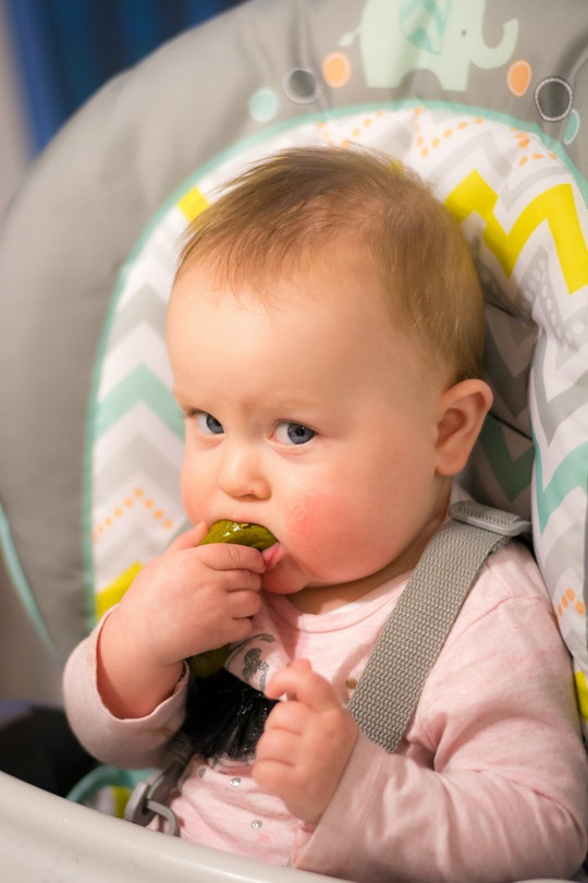Happy baby girl eating a pickle for the first time