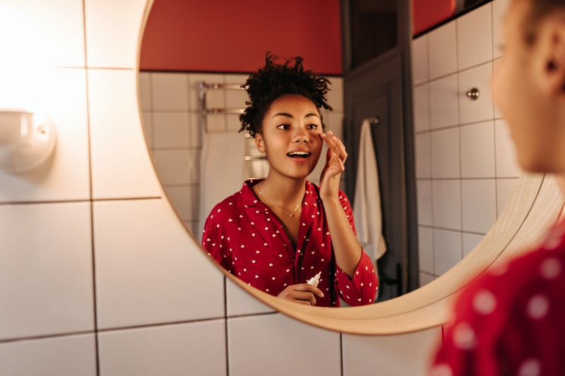 Curly woman looks in mirror and puts cream under her eyes