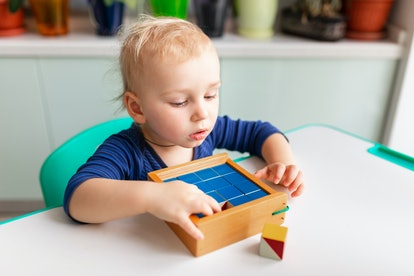 Baby playing with wooden blocks creating a pattern. Nikitin unicube game