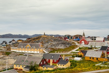 Colorful houses with the school Det gamle Sygehus, the cathedral and the statue of Hans Egede in the background, Nuuk, Greenland.