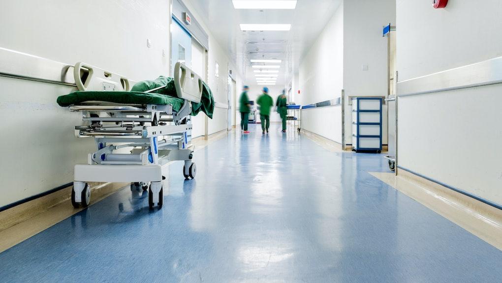 Doctors and nurses walking in hospital hallway, blurred motion.