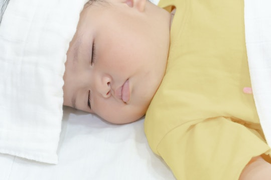 Sick baby girl sleeping with white towel at head reducing temperature