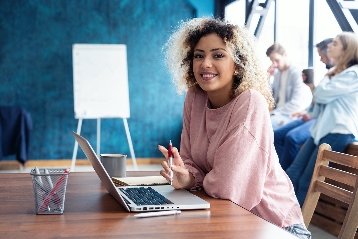 Beautiful business African lady is looking at camera and smiling while working in office. Attractive...