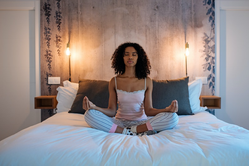 Attractive black woman sitting in lotus position on bed meditating