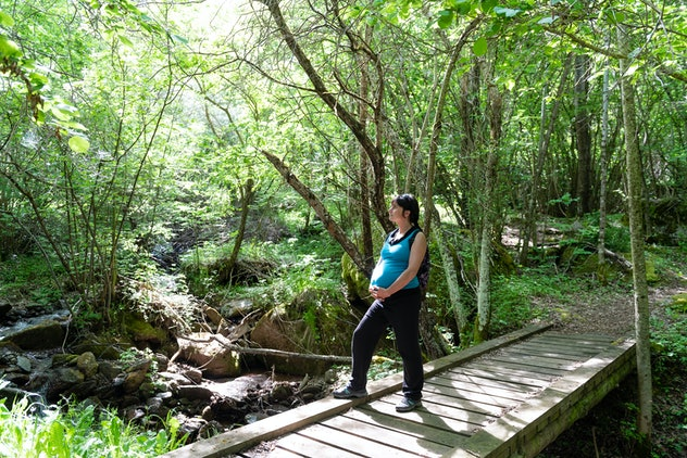 Pregnant woman walking outdoors in a forest and enjoying nature and trees.