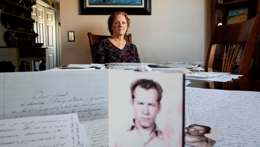 """Janet Uhlar sits for a photo at her dining room table with an arrangement of letters and pictures she received through her correspondence with imprisoned Boston organized crime boss James """"Whitey"""" Bulger, in Eastham, Mass. Uhlar was one of 12 jurors who found Bulger guilty in a massive racketeering case, including involvement in 11 murders. But now she says she regrets voting to convict Bulger on the murder charges, because she learned he was an unwitting participant in a secret CIA experiment in which he was dosed with LSD on a regular basis for 15 months"""