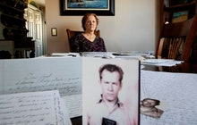 Janet Uhlar sits for a photo at her dining room table with an arrangement of letters and pictures sh...