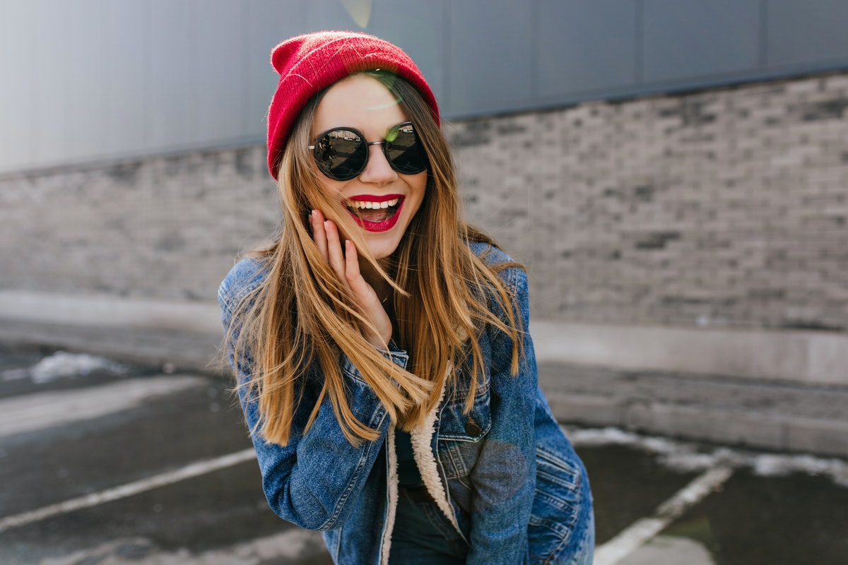 Lovable european girl in trendy black glasses laughing in spring weekend. Outdoor photo of dreamy fe...