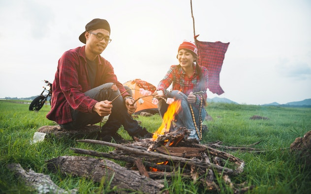 Couple lover enjoying roasting marshmallows over the fire, couple lover enjoy camping countryside with campfire, Great warm evening