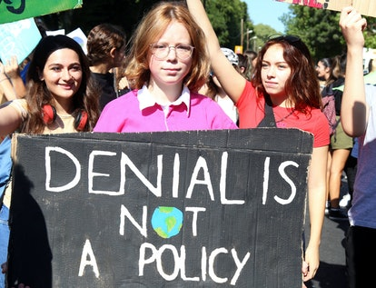 Students with a banner 'Denial is not a policy' gather for a protest against climate change in Nicos...
