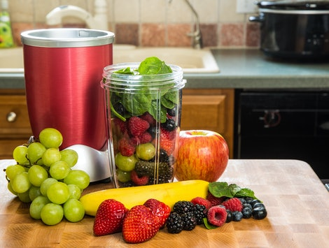 Healthy fruits with small blender on a cutting board getting ready for making a smoothie in a kitchen setting.