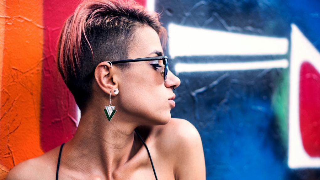 Street punk or stylish girl with pink dyed hair. Woman with piercing in nose, ears tunnels and unusual hairstyle at basketball court with graffiti paintings on walls