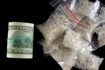 Drug trafficking crime. Addictive substance sale. Buying meth, bath salts, crack, flakka. Black market concept with a roll of dollars and drug doses on black background
