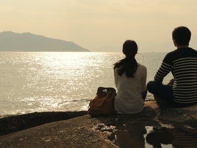 Couple enjoy the view of seascape under sunset