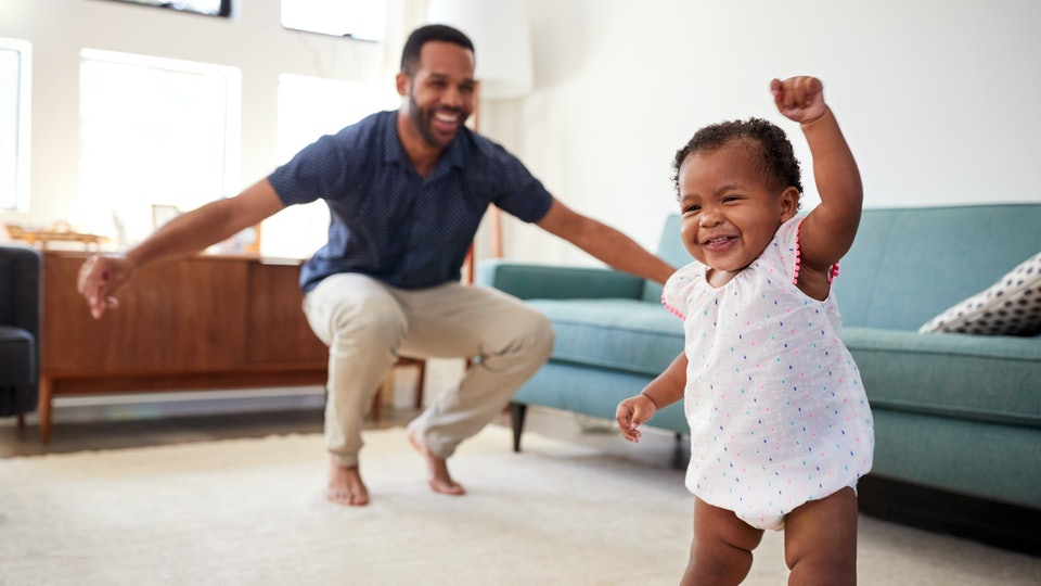 baby girl taking first steps with dad in living room