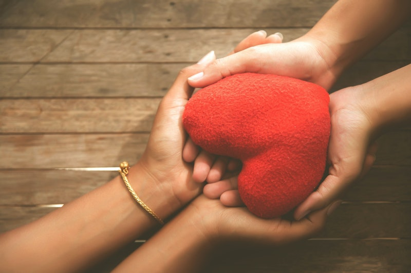 Valentine day,The hand of a beloved friend holding a red heart, health care, love, organ donation, family insurance and CSR concepts, World Heart Day, World Health Day