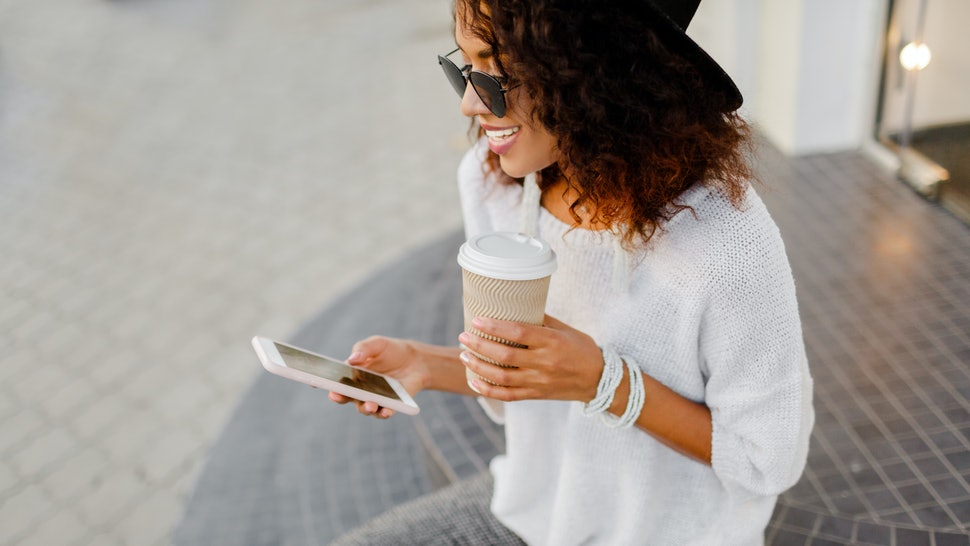 Successful black woman, blogger or store manager  using mobile phone during coffee break. Sitting on stairs and holding paper cup of hot beverage.