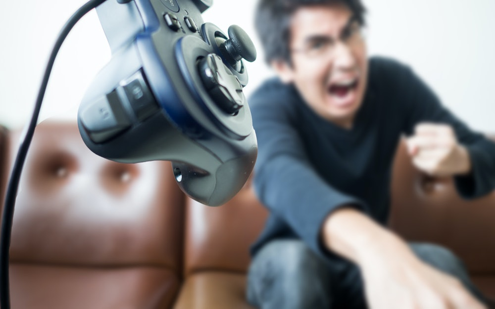 An Asian young man throwing video game controller away with anger; Concept of aggressive serious gamer get mad and failed