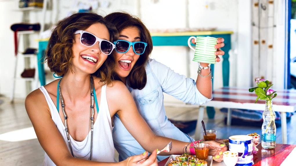Two friends wearing sunglasses smile while enjoying brunch together at a colorful, bright restaurant.