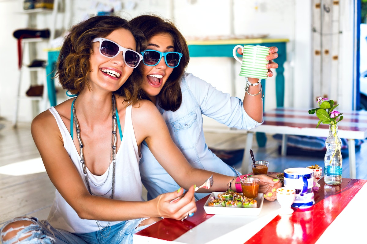 Two friends wearing sunglasses smile while enjoying brunch together at a colorful, bright restaurant...