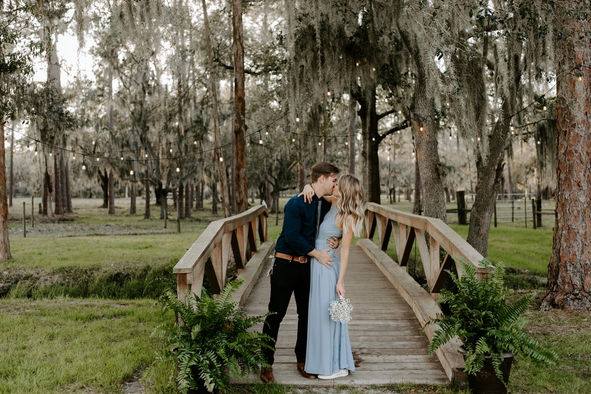 A bridesmaid in her blue dress kisses her date at a wedding while standing on a bridge under string lights and trees.