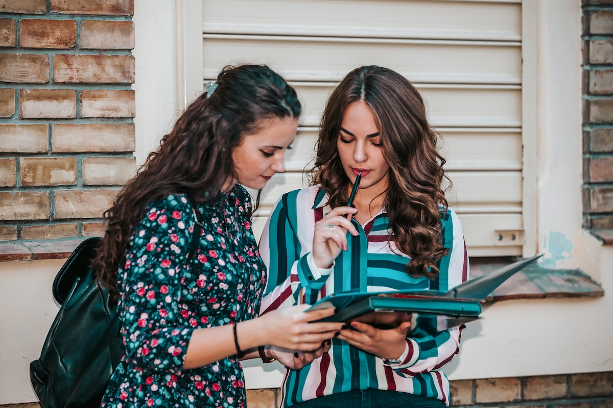 Two female friends - students reading a notebook and commenting in the street.