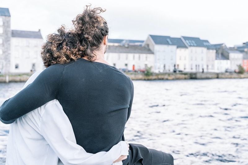 Stock photo of a Young couple hugging with their backs looking at the sea and the buildings in the background. Lifestyle