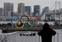 A pedestrian watches the Olympic Rings monument on a vessel being installed at Odaiba, Tokyo, Japan,...