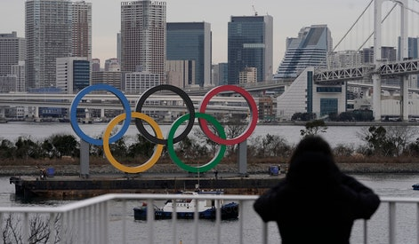 A pedestrian watches the Olympic Rings monument on a vessel being installed at Odaiba, Tokyo, Japan, 17 January 2020. At Odaiba Marine Park, the Olympic aquatic events of marathon swimming and triathlon will be held. Tokyo 2020 Olympic Games will open on 24 July through 09 August 2020.