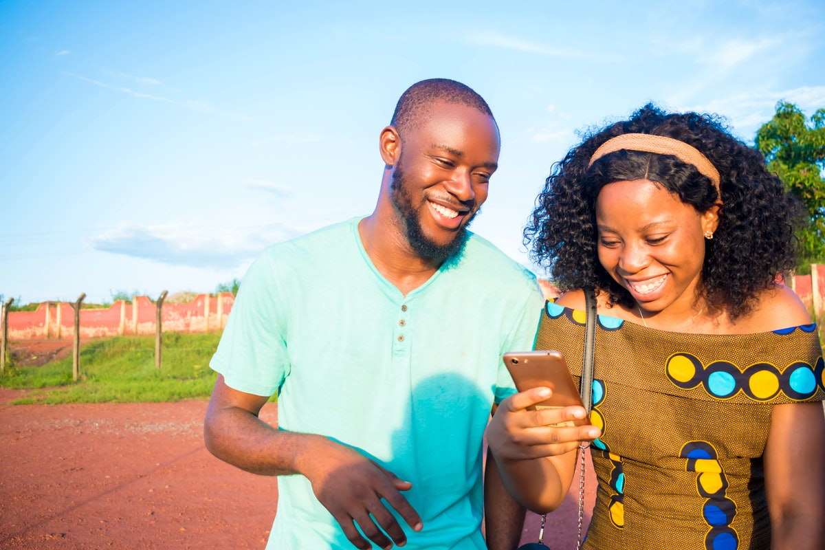 Two friends look down at a phone and laugh while walking on a pathway on a sunny summer afternoon.