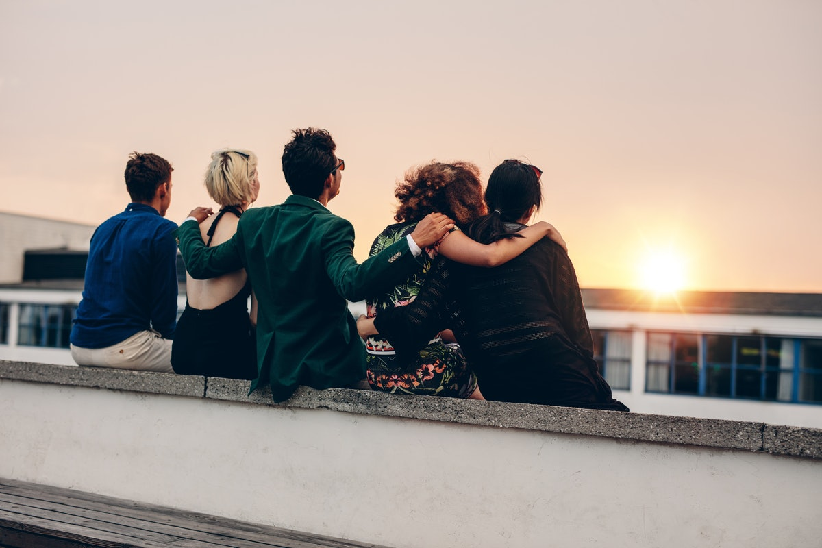 Rear view of young men and women relaxing together on rooftop and looking at sunset. Multiracial friends sitting on terrace in evening.