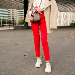 Street fashion autumn details of young progressive  hipster business woman, red pants, funny socks and trendy ugly sneakers, beige classic coat, modern buildings around, phone and accessories.
