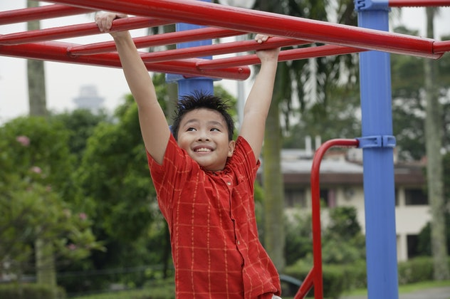 Boy using the jungle gym at playground