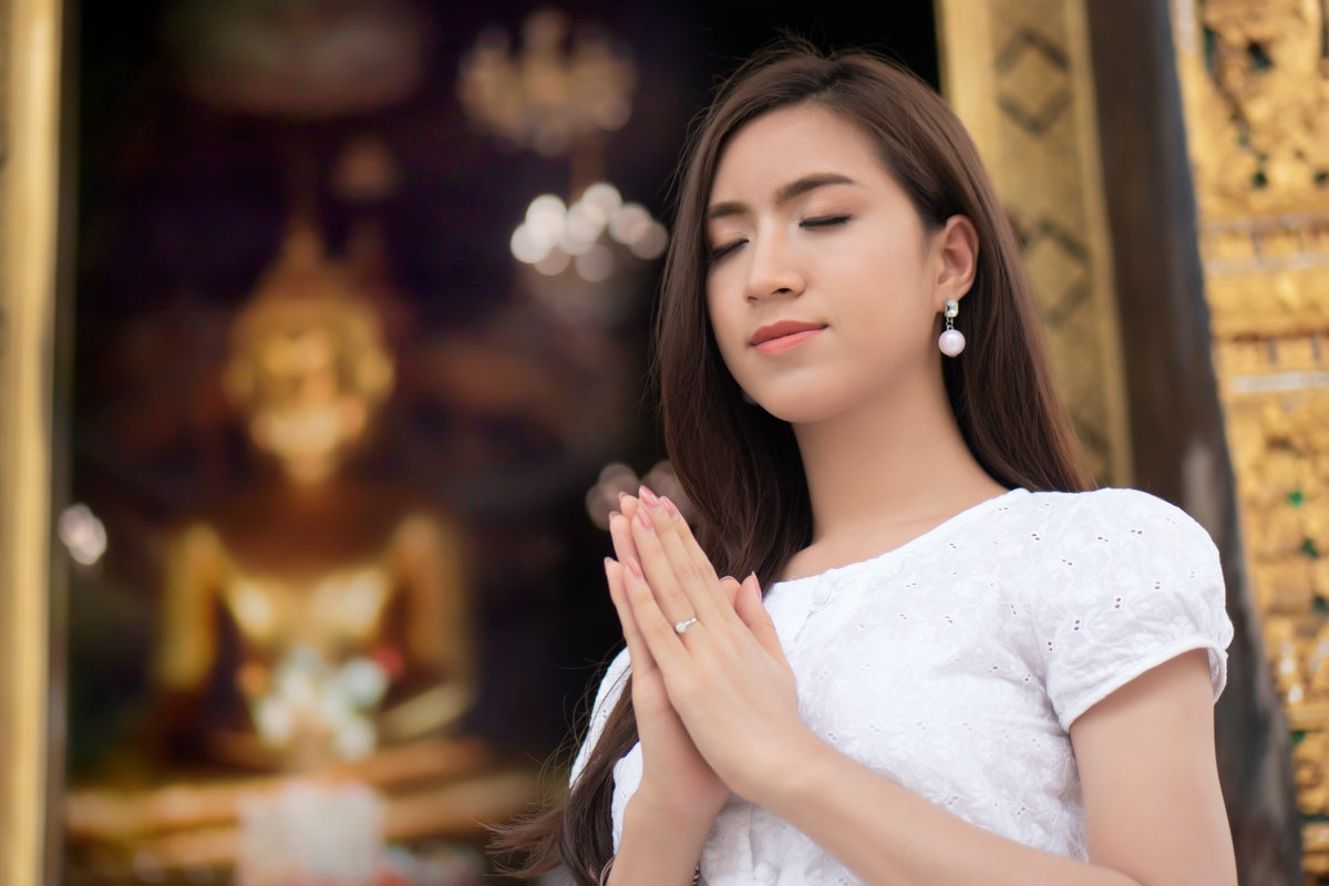 Religious Asian buddhist woman praying. Female buddhist disciple meditating, chanting mantra with pr...
