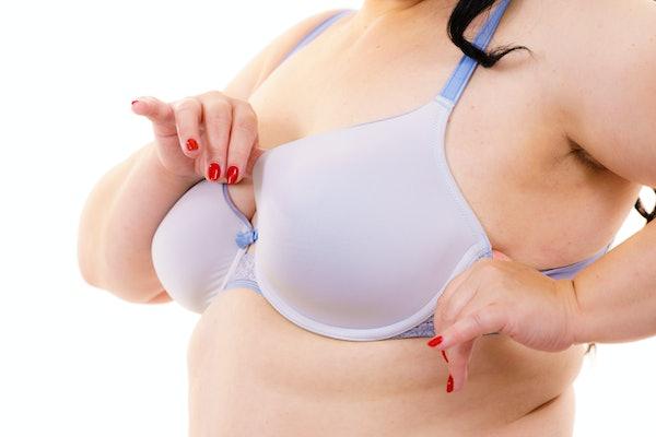 Plus size fat mature unrecognizable woman wearing bra, on white. Female breast in lingerie. Bosom, brafitting and underwear concept.