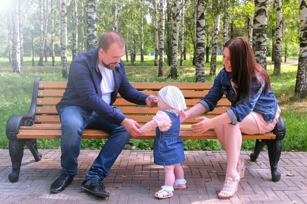 Happy family walking at weekend. Parenthood and baby care. Baby girl is trying to make first steps from mom to dad holding hands sitting on bench in park. Parents learning daughter to walk.
