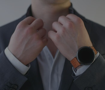 Man in a suit with a wrist watch.