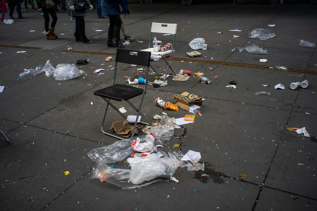 People walk by litter on the ground after the Macy's Thanksgiving Day Parade, in New York