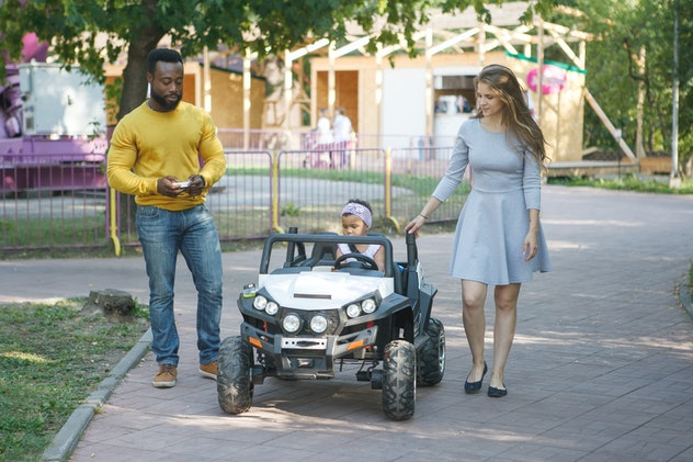 Little cute girl riding a toy car in the summer park on the track. Mother and father walk alongside, helping in the movement.