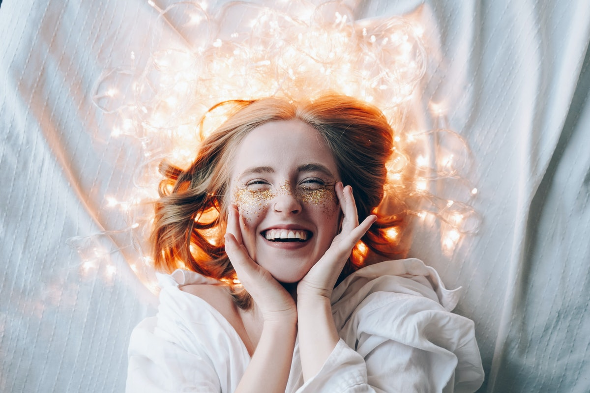 A young girl with sparkles on her cheeks lies and smiles. Christmas lights glow around. Holidays