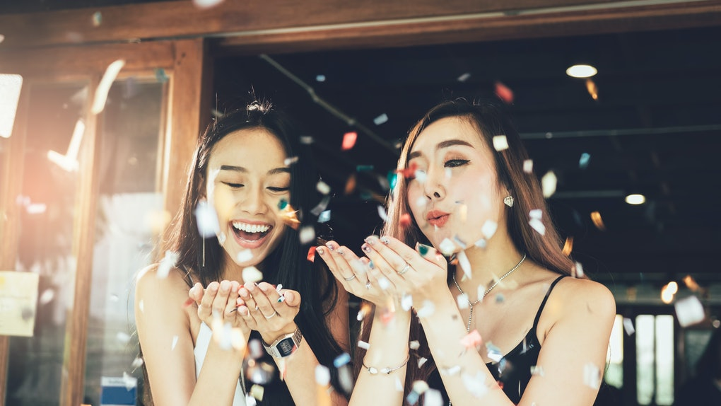 Two women in dresses blow confetti in the air at a restaurant while celebrating a birthday.